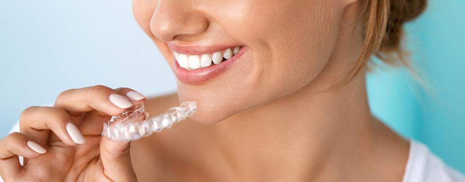 woman holding teeth whitening kit