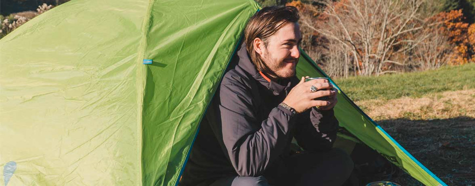 man drinking coffee while camping