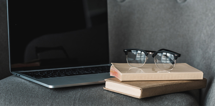 business books, glasses and laptop