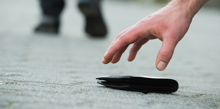 man picking up a wallet