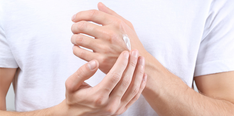 man putting hand cream on