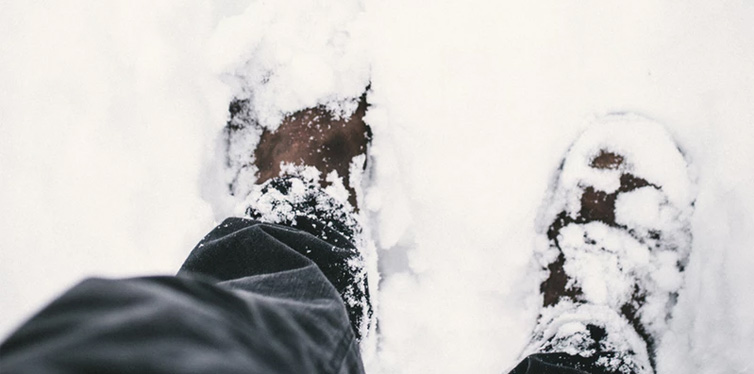 man standing in snow wearing winter shoes