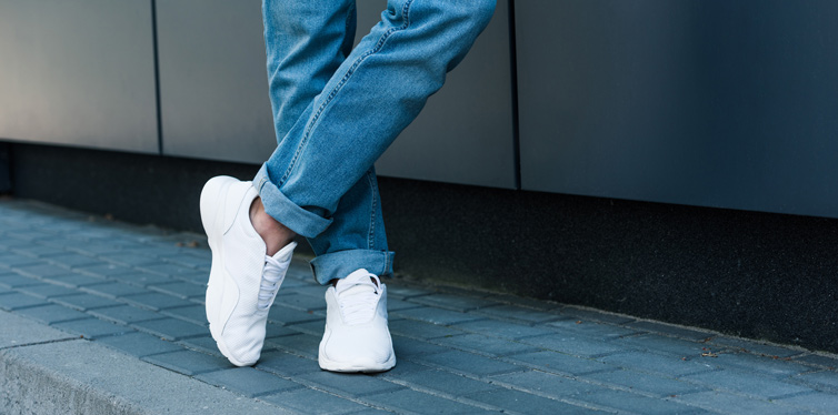 man wearing white sneakers and jeans