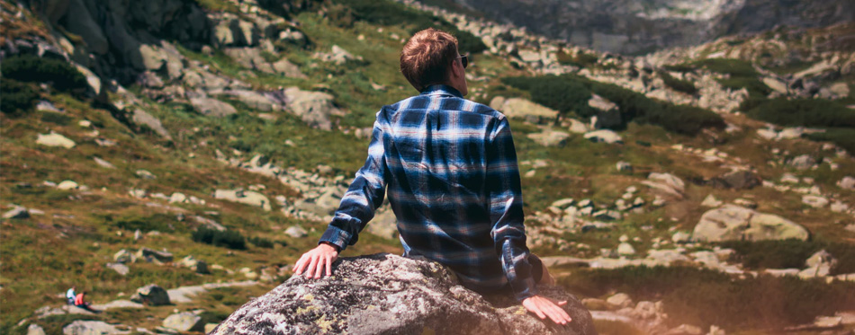 man in flannel shirt sitting in the mountains