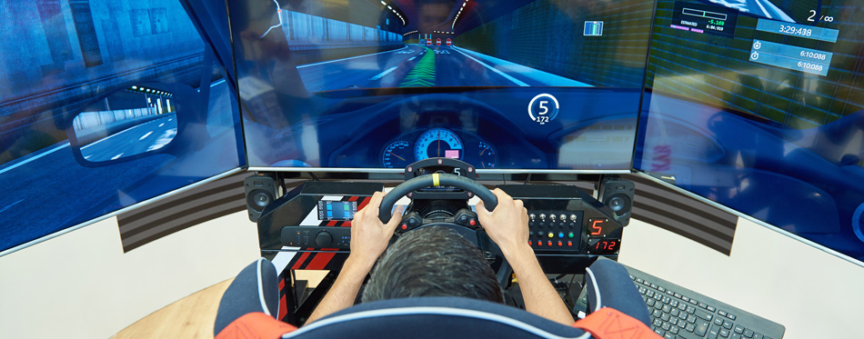 boy playing game using racing wheel