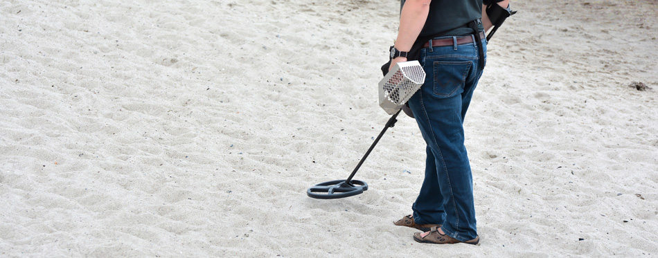 man using metal detector on the beach