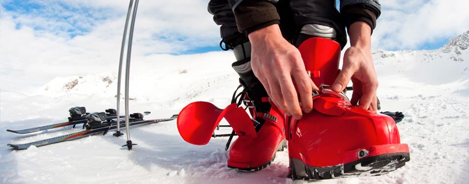 man wearing red ski boots