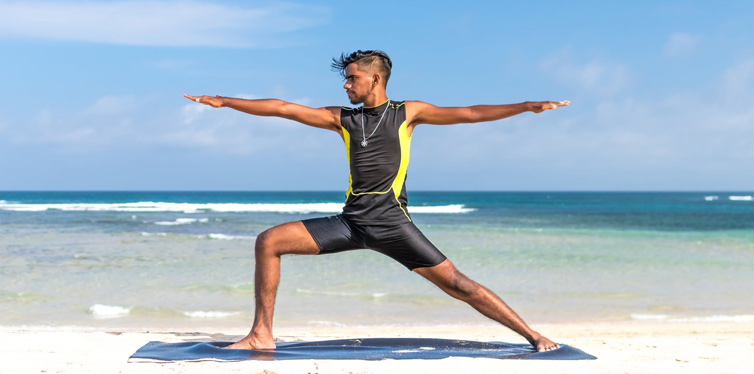 man doing yoga at the beach