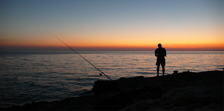 man fishing in sunset