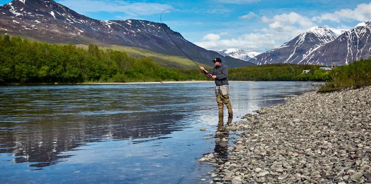 man on the river bank fishing
