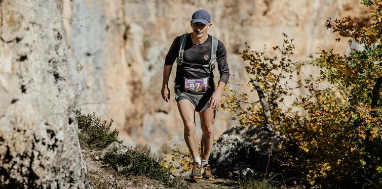 man on trail running uphill