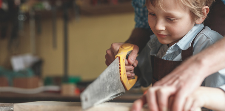 kid learning to saw