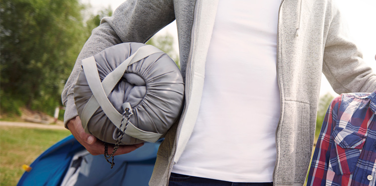 man holding a sleeping bag