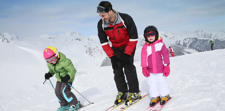 man with two kids skiing