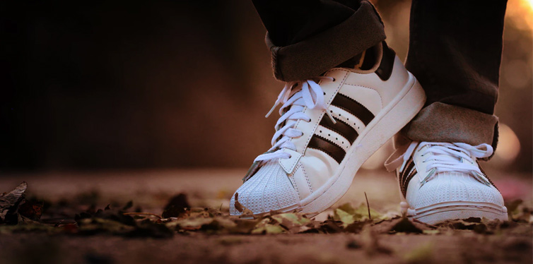 man wearing adidas sneakers