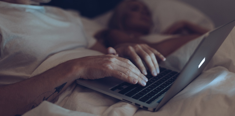 man looking at the computer in bed