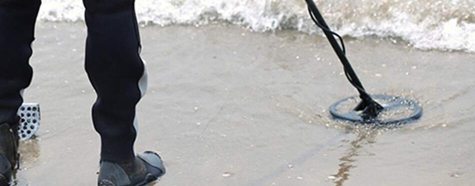 man using an underwater metal detector