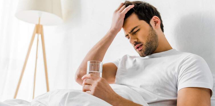 man with headache holding glass of water