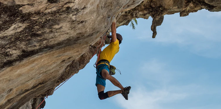 a rock climber hanging off a rock