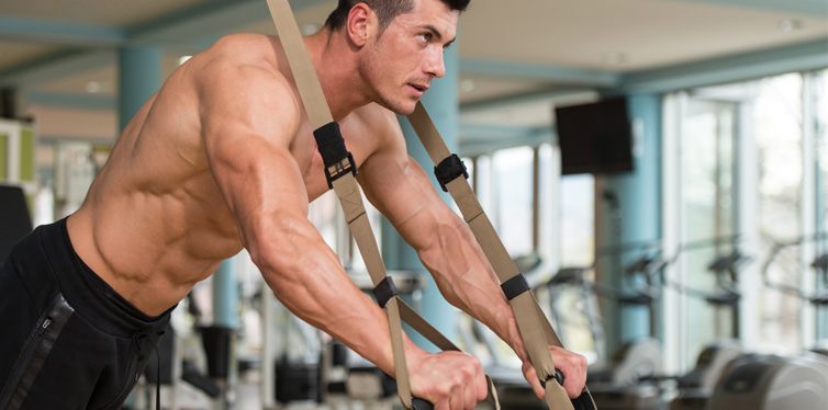 athletic man doing trx exercises