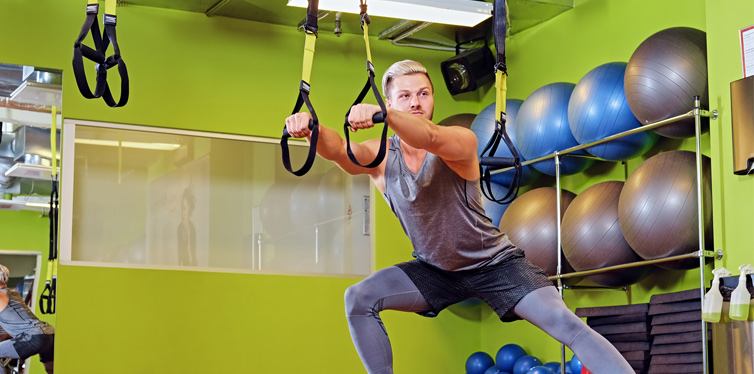 man doing trx workout at the gym