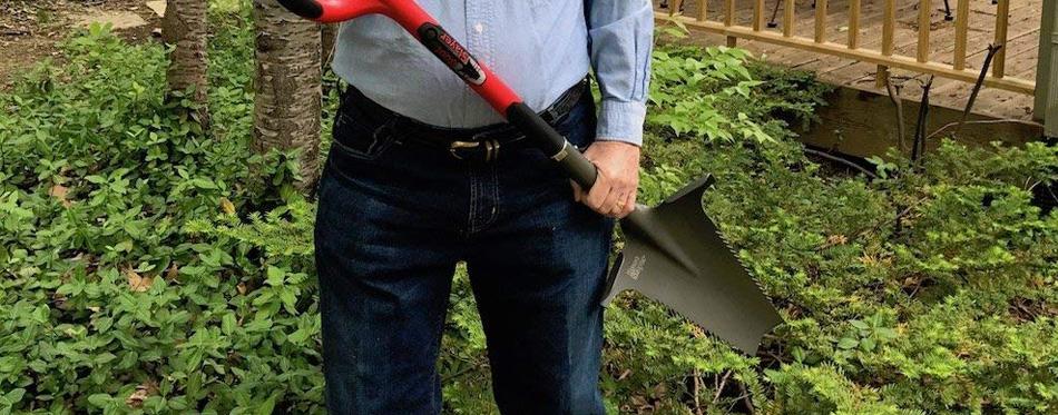 man holding a garden shovel