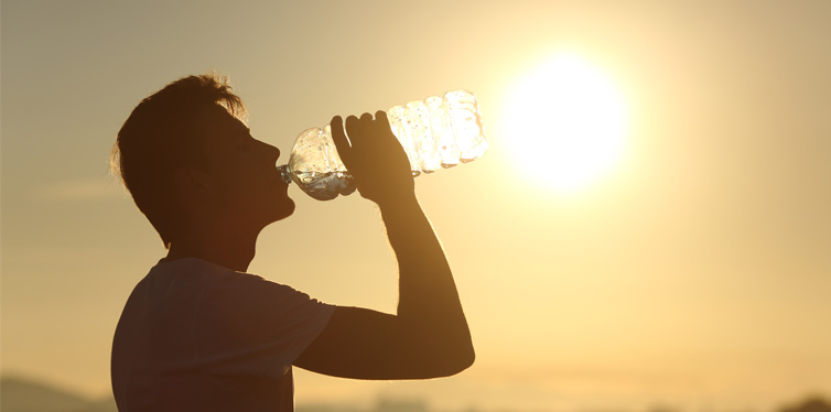 man drinking water on a hot day