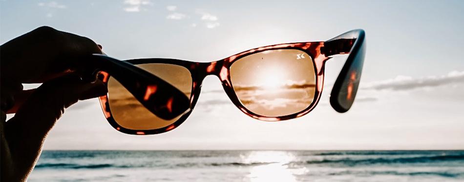 man holding polarized sunglasses