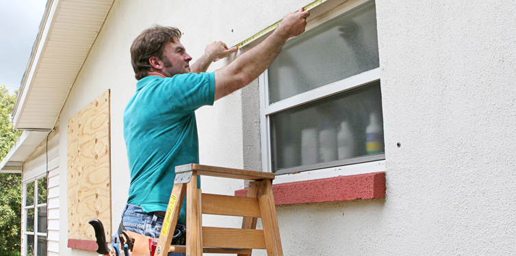 man repairing windows of his house