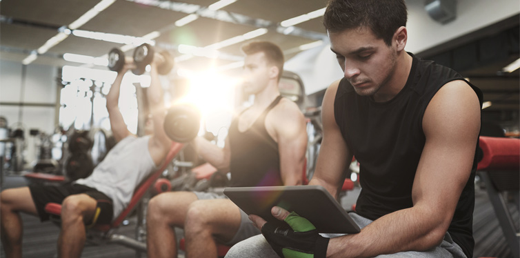 man holding tablet at the gym